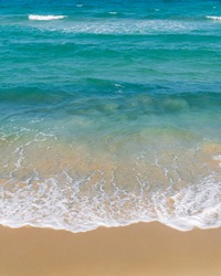 Sand beach seashore vertical with white foamy and blue wave from the sea on summer season