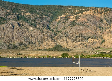 Sand beach with installed valleyball net for the game. Okanagan lake view with mountain background