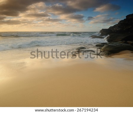 Sand beach with soft and smooth water and clouds and some rocks and with wide sand line