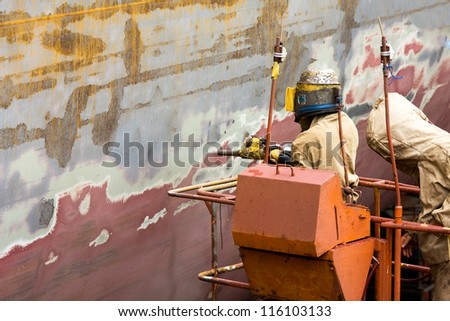 Sand blasting of the container ship's hull on the dry dock.