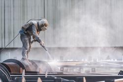 Sand blasting process, Industial worker using sand blasting process preparation cleaning surface on steel before painting in factory workshop.