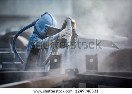 Sand blasting process, Industial worker using sand blasting process preparation cleaning surface on steel before painting in factory workshop.