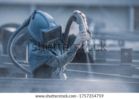 Photo of  Sand blasting process, Industial worker using sand blasting process preparation cleaning surface on steel before painting in factory workshop.