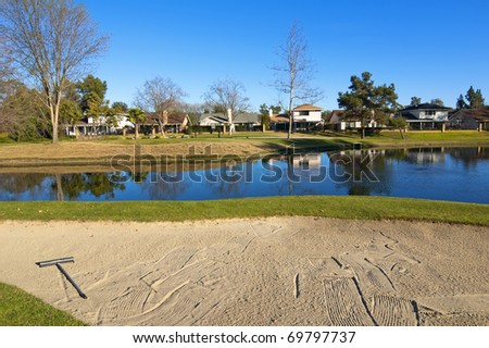 Sand bunker on the golf course with green grass, trees and pond