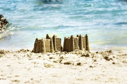 Sand castle on sandy beach near waving blue sea. Playing with sand and building sandcastle on seashore. Summer vacation concept.