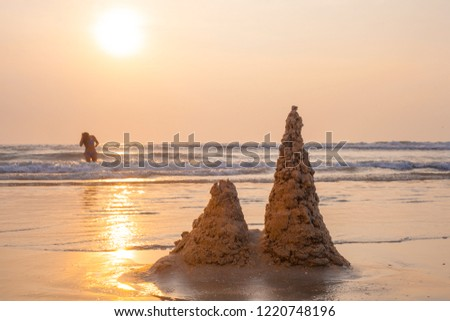 Sand castle on the beach on sunset. Seaside scene in grey and yellow colors.