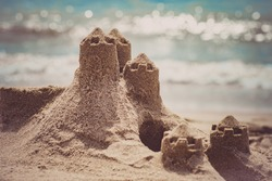 Sand castle standing on the beach. Travel vacations concept.