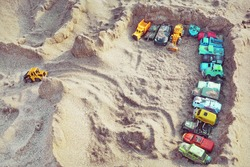 Sand Castle Top View On Sea Beach With Kids Toys. Sand Castle Or Fort With Many Colorful Plastic Car On Summer Sea Coast Overhead View. Abstract Background.