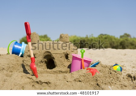 Sand castle with toys at the beach - stock photo
