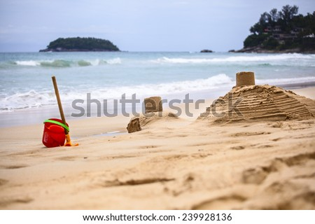 Sand castles made by children on the background of the sea #239928136
