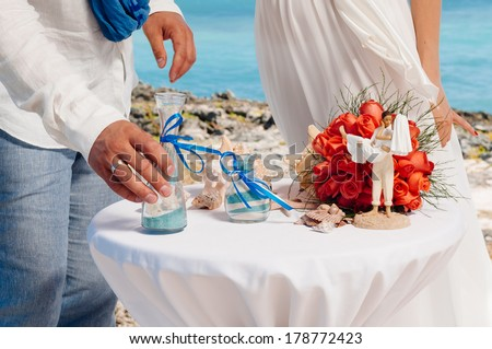 sand ceremony being performed at wedding. Hands of bride holding vase with colorful sand during wedding party