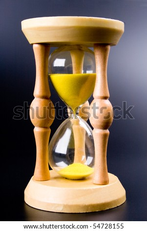 sand clock showing how is time passing on black background