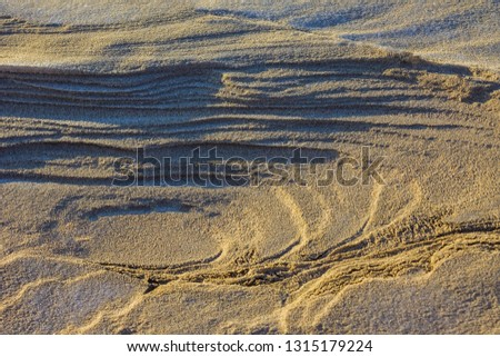 Sand, desert, layered structure. A thin layer of white snow. Lateral solar lighting. #1315179224