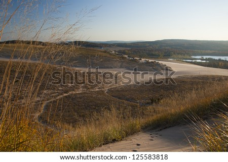 Sand dune landscape in Autumn with lake and farm in distance