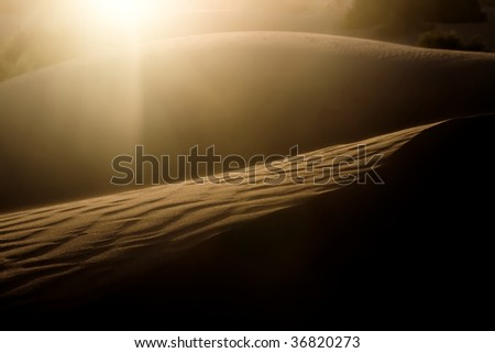 Sand dune on the sunset with sun flare