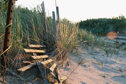 Sand Dune with broken wooden snow fence at sunset.