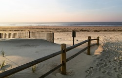 Sand dunes, a wooden fence on a background of blue ocean, ocean city, NJ