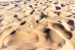 Sand dunes for Desert Safari in Dubai, United Arab Emirates. Beautiful wild sand dune with the wind blowing in the desert of Dubai at sunset. Dubai is famous for Desert Safari, Dunes Bashing in world.