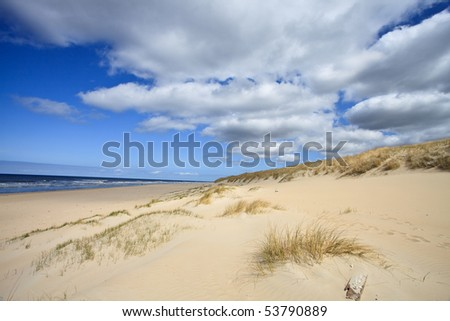 Sand dunes near to the sea with cloudy sky