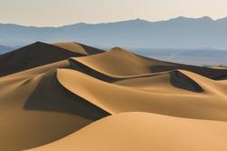 Sand dunes over sunrise sky in Death Valley, California