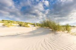Sand dunes with grass under a blue sky with clouds