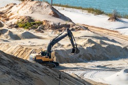 Sand extraction with machinery excavator at quartz quarry close-up. Sand dunes hills terrain digging near lake