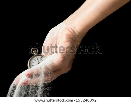 Sand flowing between fingers of a hand holding an antique pocket watch