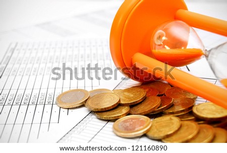 Sand-glass and coins on documents.