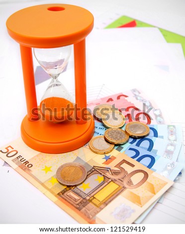 Sand-glass, coins and euro on graphs.
