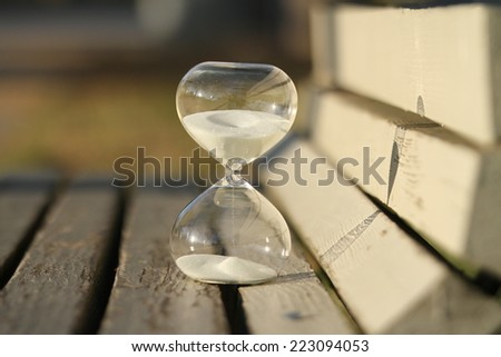 sand-glass. Modern hourglass on a bench in a park. symbol of time. countdown.