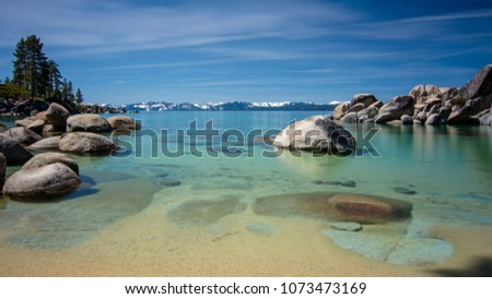Sand Harbor at Lake Tahoe North, Nevada county, California, USA, featuring blue transparent water, rocky shore and snow on tops of background mountains on a blue sky day with few clouds