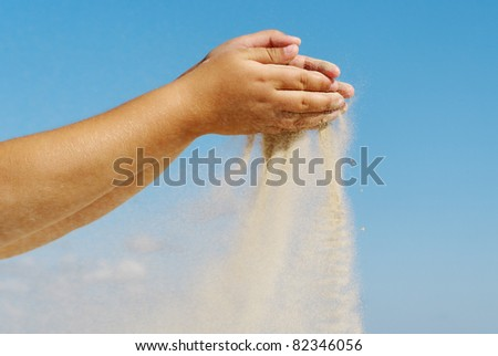 Sand is pouring out from a girl hands on sky background.