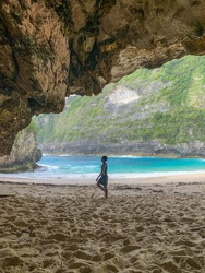 Sand on cave entrance. View from the cave. the cliff background. Happy tourist man standing & walking on sand on beach  ,beach,keling king,T-Rex Bay,Nusa Penida Island,Bali,Indonesia,frame, texture