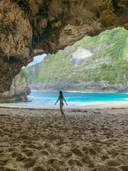 Sand on cave entrance. View from the cave. the cliff background. Happy tourist woman standing & walking on sand on beach  ,beach,keling king,T-Rex Bay,Nusa Penida Island,Bali,Indonesia,frame, texture