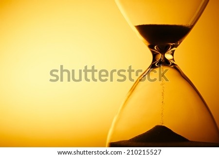Sand passing through the glass bulbs of an hourglass measuring the passing time as it counts down to a deadline or closure on a yellow background with copyspace #210215527