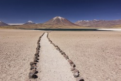sand path to mountain lake with blue sky in atacama chile