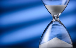 Sand running through an hourglass measuring passing time counting down towards a deadline, close up view of the glass bulbs with and copy space