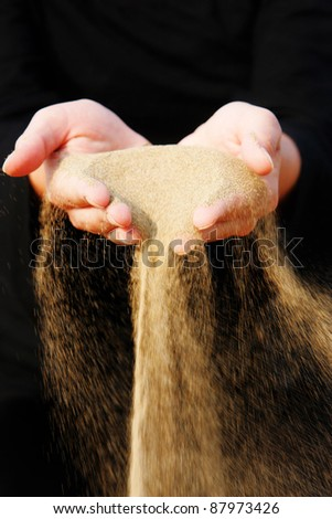 sand running through hands as a symbol for time running, lost etc.............