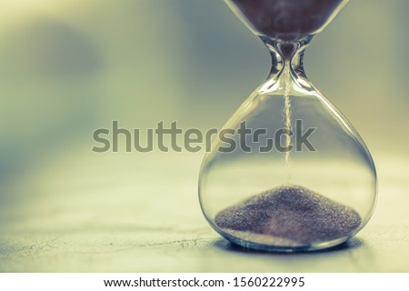 Sand running through the bulbs of an hourglass measuring the passing time in a countdown to a deadline, on a bright background with copy space.
