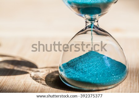 Sand running through the bulbs of an hourglass measuring the passing time in a countdown to a deadline, on a bright wooden background with copy space. #392375377
