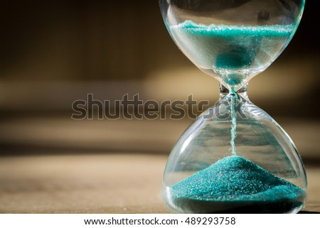 Sand running through the bulbs of an hourglass measuring the passing time in a countdown to a deadline, on a dark background with copy space. #489293758