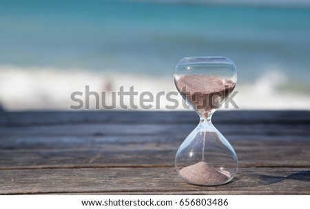 Sand running through the bulbs of an hourglass measuring the passing time in a countdown to a deadline. Beach and sea background, concept for vacation countdown. Time for relaxation. #656803486