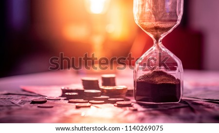 Sand running through the shape of hourglass on table with banknotes and coins of international currency. Time investment and retirement saving. Urgency countdown timer for business deadline concept #1140269075