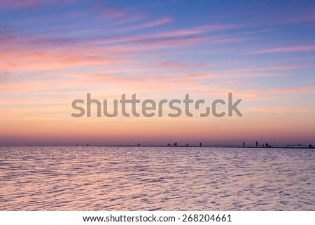 Sand spit in the blue sea and people silhouettes on a background picturesque purple sunset in the summer evening