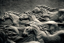 Sand stone sculpture brick wall of herd horse run background, low key black and white, high contrast and hard lighting tone