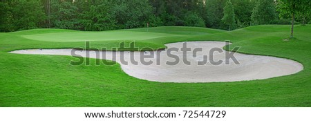 sand trap on the green grass of the golf course
