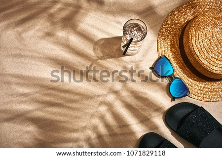 Sandal, straw hat and sunglasses on a sandy background, top view