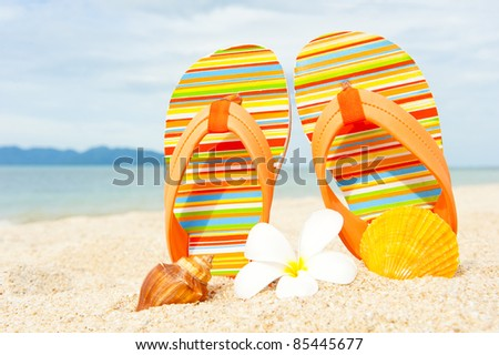Sandals at the beach near the water line - stock photo