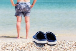 Sandals, clogs on the shell seaside. Against a background, a person in swimming trunks goes into the water.