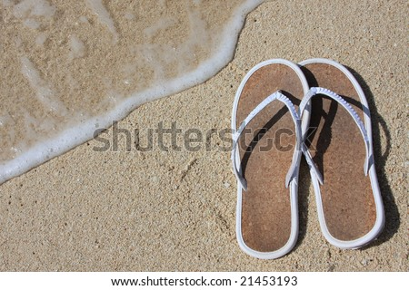 Sandals on beach sand with high tide